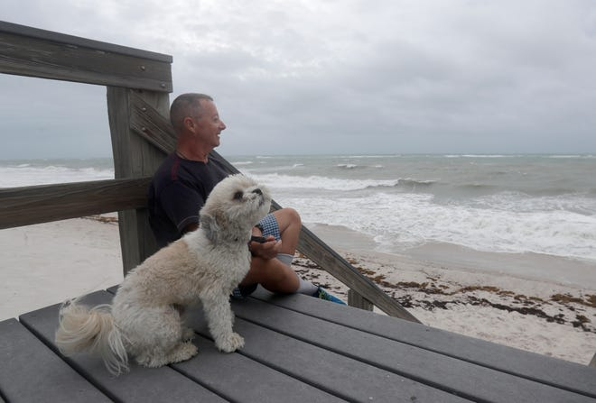 Kent Ahern and his dog Blanco watch waves churned up by Tropical Storm Isaias near Jaycee Beach Park, Sunday, Aug. 2, 2020, in Vero Beach, Fla. Isaias weakened from a hurricane to a tropical storm late Saturday afternoon, but was still expected to bring heavy rain and flooding as it barrels toward Florida. (AP Photo/Wilfredo Lee)
