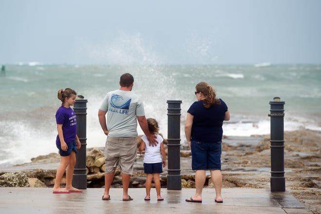 Elizabeth Whittemore, left, along with her father, James; sister, Jordan; and mother, Susan, stand at the end of the South Jetty in Fort Pierce, Fla., on Sunday to watch the waves crash over the rocks brought by the high winds of Tropical Storm Isaias. [Patrick Dove/TCPalm.com via AP]