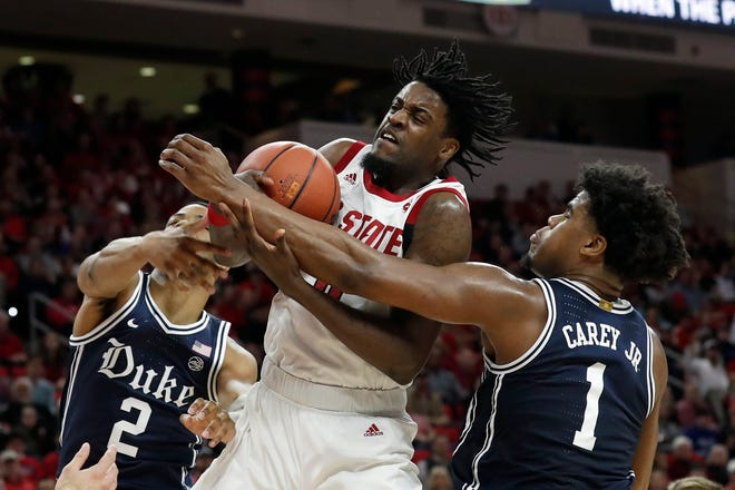 N.C. State's D.J. Funderburk grabs a rebound in traffic between Cassius Stanley, left, and Vernon Carey Jr., right, of Duke during the Wolfpack's victory in February. [The Associated Press]