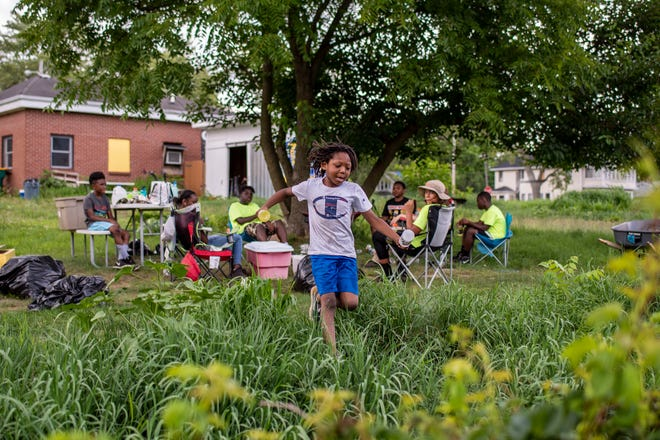 Devon Wilson's younger cousin Logan Knox, 6, skips through the grass at Sunlight Gardens during a youth gardening club on Wednesday, July 29, 2020 in Battle Creek, Mich. Sunlight Gardens will be hosting a community block party on Sept. 17.