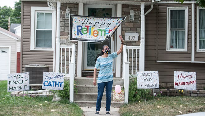 Chillicothe native Cathy Fairrow waves at passerbies as her front lawn is decorated to celebrate her more than forty years of service. Fairrow recently retired from the Chillicothe VA.