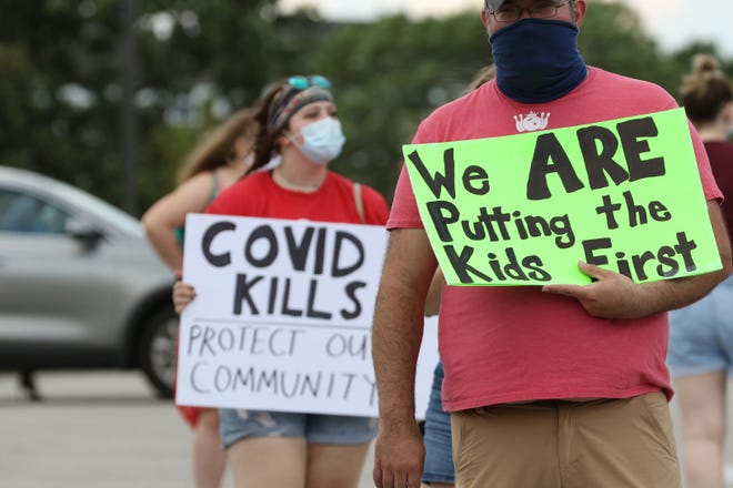 Protesters gather outside a Cincinnati Public Schools board meeting while the board decides the reopening plan for the schools, Aug. 3, 2020. Protesters want an exclusively virtual learning plan.