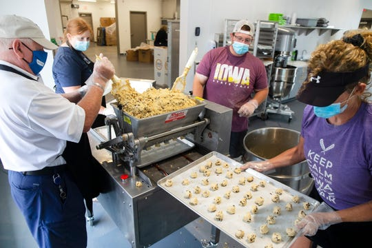 "Roger Mortvedt, Cody Marsh, and Stacy Jorgensen prepare cookies on July 31, 2020 at the Iowa State Fairgrounds. Two ""dropper"" dough machines are capable of preparing nearly a thousand cookies an hour."