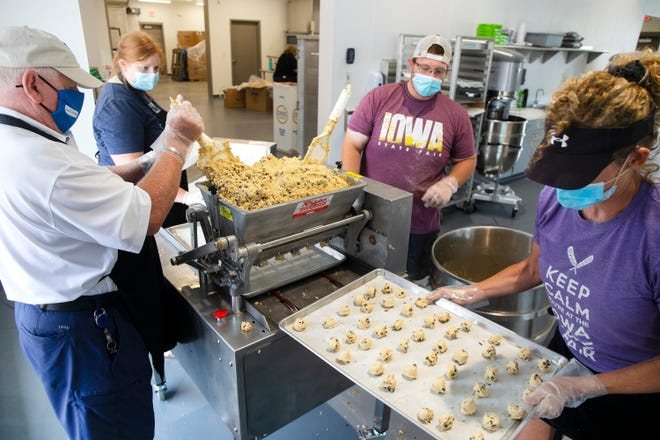 """Roger Mortvedt, Cody Marsh, and Stacy Jorgensen prepare cookies on July 31, 2020 at the Iowa State Fairgrounds. Two """"dropper"""" dough machines are capable of preparing nearly a thousand cookies an hour."""