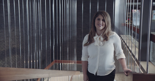 Bianca Iacopelli is a creative designer at GM, where she works on the badging, graphics, and logos team. Here, she stands in the lobby of GM Design.