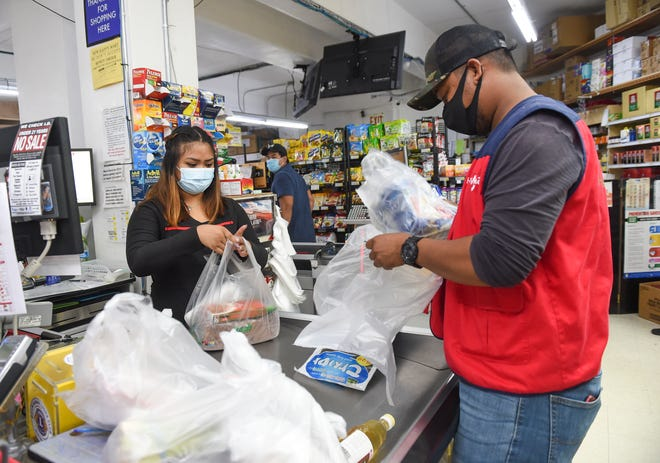 Employees Roucell Bautista and Josiah Gustaf bag groceries during a shift at Super Happy Mart in Barrigada, Aug. 3, 2020.