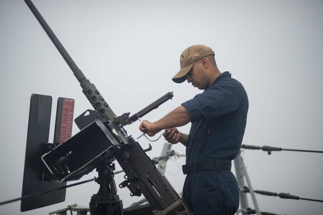 Navy Gunner's Mate Seaman Gerald Turner uses a head space and timing gauge on a M2 heavy barrel machine gun to a mount aboard the Arleigh Burke-class guided-missile destroyer USS Rafael Peralta in this file photo provided by the Navy. The Navy in a news release said Turner, 23, a gunner's mate seaman, died last Thursday on Guam.