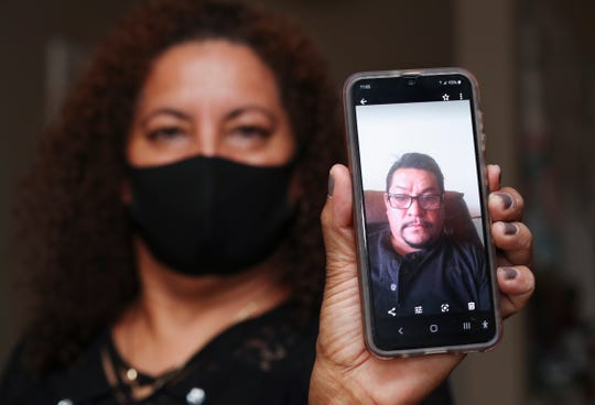 Alvina Baires displayed an image of her partner, Juan Carlos Pat Morales, who died from COVID-19 in April on Aug. 2, 2020.  She received help from a chaplain to help her navigate the language barriers during the process.