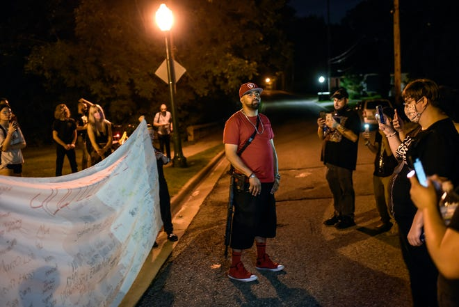 Paul Birdsong, center, and a group of protesters stand outside Mayor Andy Schor's house on Sunday, Aug. 2, 2020, in Lansing. The protest was organized by We the Free People of Lansing.