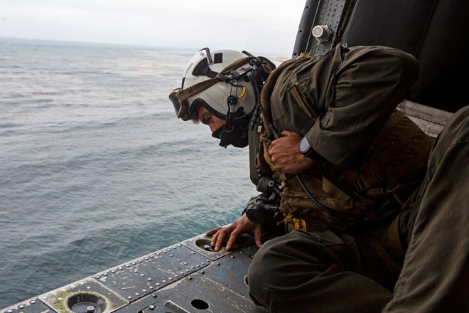 Naval Air Crewman (Helicopter) 2nd Class Joseph Rivera, a search and rescue swimmer, looks out of a U.S. Navy MH-60 Seahawk while conducting search and rescue relief operations following an AAV-P7/A1 assault amphibious vehicle mishap off the coast of Southern California on July 30, 2020. The families of the nine people who died in the accident are suing the manufacturer of the AAV, BAE Systems, arguing that the contractor knew about the flaws the families believe are responsible for the deaths of their sons.