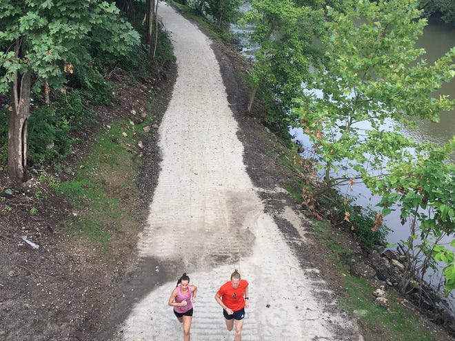 Two runners head under the Walnut Street Bridge on the  new Central Levee Trail, which remains under construction, on Monday, Aug. 3, 2020.