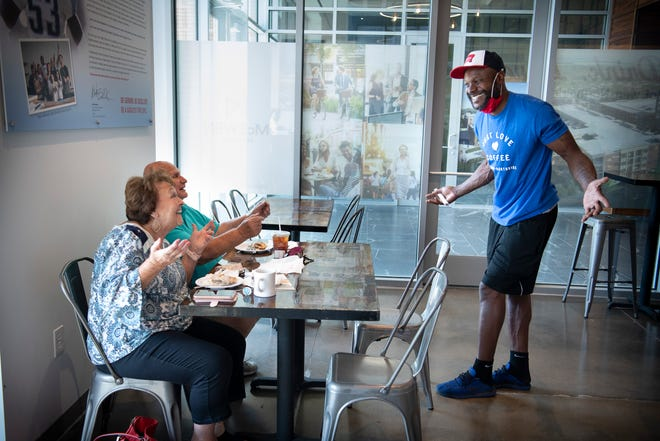 Former Tennessee Titan Keith Bulluck visits with customers Lois and Jake Flaker as they enjoy breakfast at his Just Love Coffee in Franklin, Tennessee, on Monday, Aug. 3, 2020.