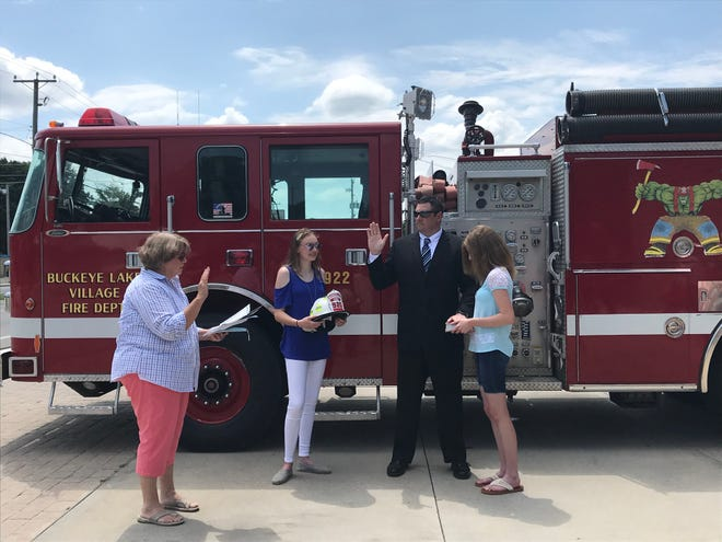 Ryan Wyse raises his hand to be sworn in as Buckeye Lake's new fire chief by Buckeye Lake Mayor Peggy Wells at the Buckeye Lake Fire Department on Friday, July 31, 2020. Wyse's daughters,  Hailey and Emma, hold his helmet and a Bible at his side.