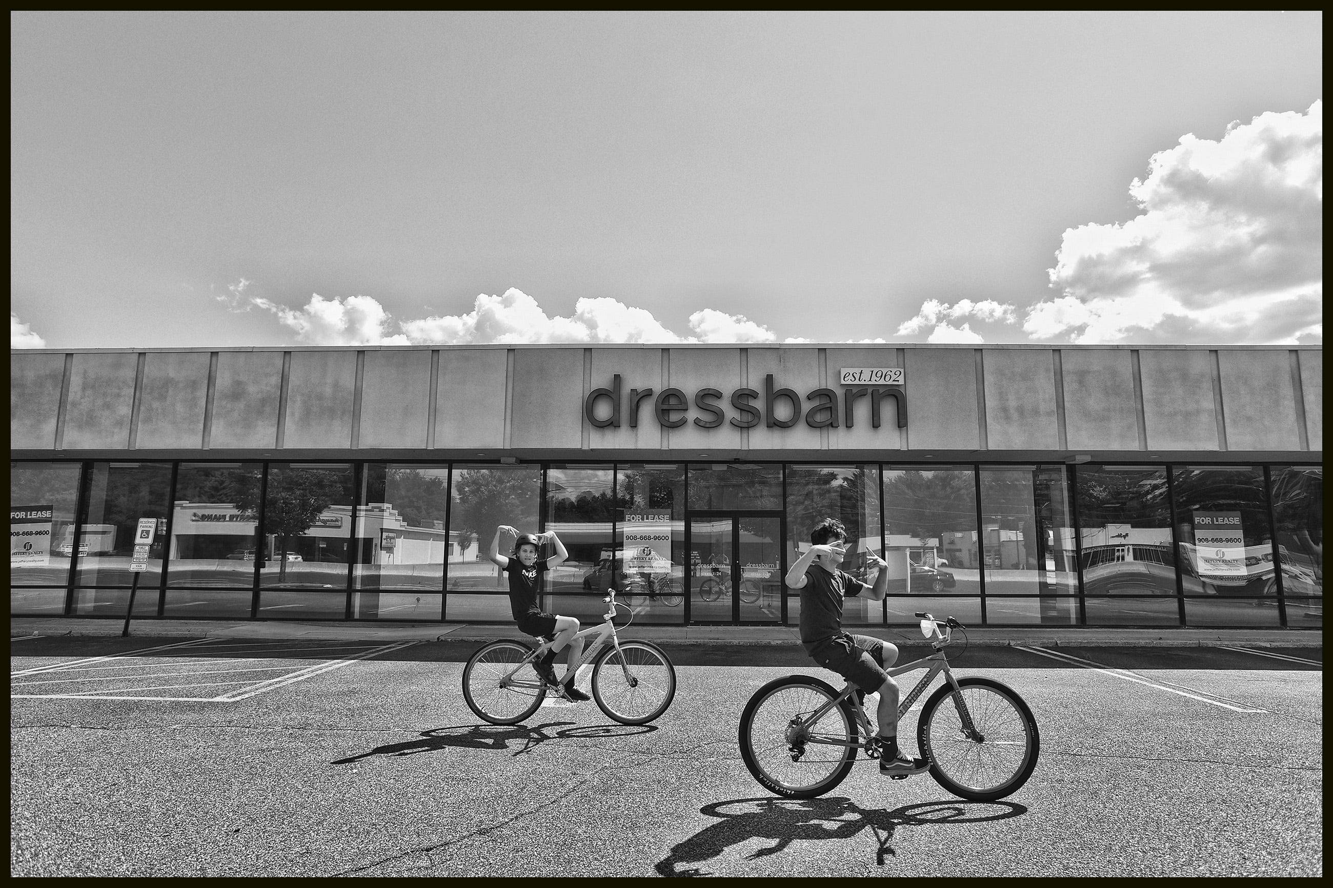 Two kids bikes ride through the empty parking lot in front  of  Dress Barn Empty in Paramus on 7/14/20.