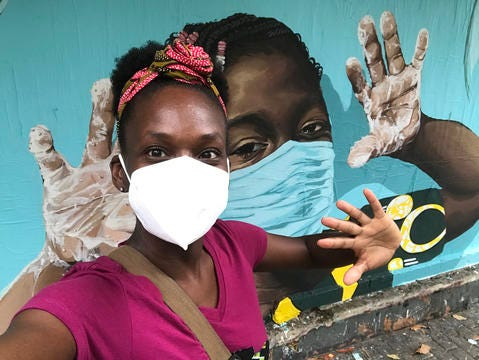 Yoruba Mitchell, a community health educator for Doctors Without Borders, poses in front of a mural the organization commissioned in Puerto Rico this spring. Mitchell, a Michigan native, has been teaching about how to prevent spread of the coronavirus.