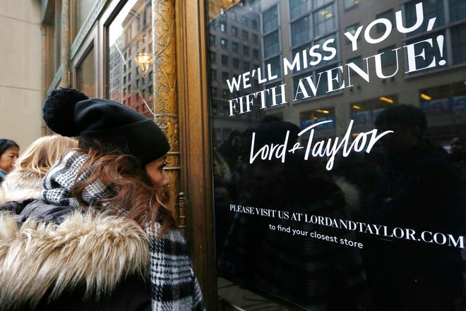 FILE - In this Jan. 2, 2019, file photo, women peer in the front door of Lord & Taylor's flagship Fifth Avenue store which closed for good in New York. New York landmark retailer Lord & Taylor has filed for bankruptcy, joining a growing list of retailers flummoxed by the pandemic. (AP Photo/Kathy Willens, File)