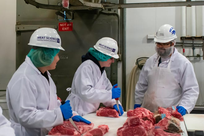 Wolf Pack Meats director Amilton de Mello, right, instructs meat science students at the plant run by the University of Nevada, Reno. The plant, one of only two USDA certified in Nevada, has continued to operate under safety guidelines so area ranchers can get their meat to market.