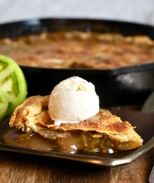 A slice of green tomato pie topped is topped with a scoop of vanilla ice cream.