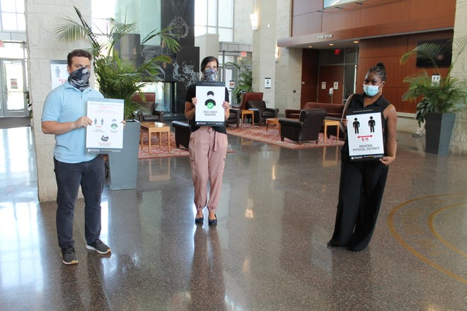 Stockton University employees display signs with information regarding COVID-19 safety precautions. The signs will be posted throughout the campus as part of preparations for the return of students to campus this fall.
