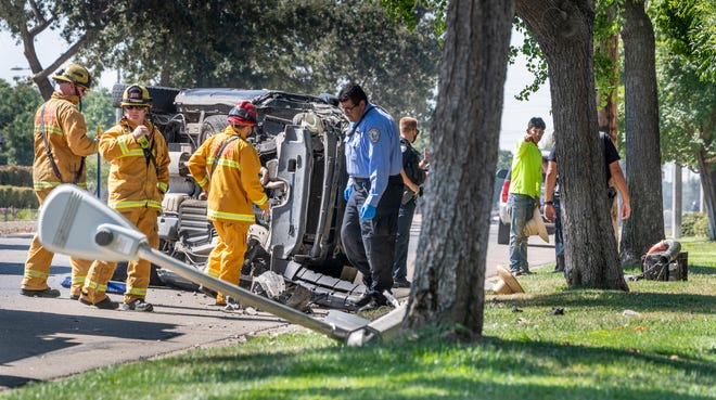 Visalia Police and Fire investigate a single car collision on Lovers Lane south of Walnut Avenue on Monday, August 3, 2020. The Honda Pilot left the roadway, sheered off a light pole and struck two landscape workers on the sidewalk as it rolled along. The pedestrians received minor injuries, the driver was transported with minor to moderate injuries and was suspected of DUI.