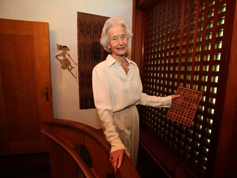 "Martha Nierenberg holds a wooden Dansk trivet, which was the inspiration for many of the lattice walls in her Westchester home. ""We put them wherever we didn't want the glass to show,"" she told The Journal News in 2013. Nierenberg, who passed away in June 2020, sold the house after her husband's death in 2009."