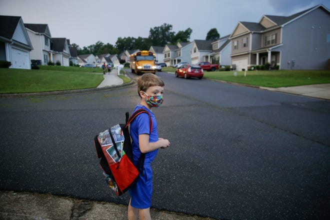 Paul Adams, 7, waits at the bus stop for the first day of school on Aug. 3, 2020, in Dallas, Ga.  Neighboring states arrived at differing conclusions on who's in charge of the reopening of schools. The differences in philosophy underscore some of the difficulties facing states as they grapple with how to proceed amid growing coronavirus infections in numerous states.