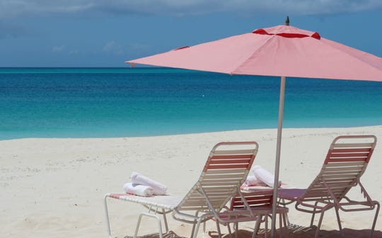 Beach loungers with signature pink umbrellas at Ocean Club Resorts in Turks and Caicos Islands.