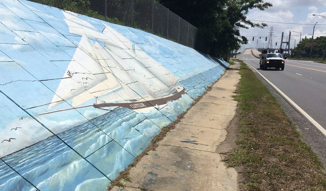 In this May 30, 2019  photo, traffic passes a mural of the slave ship Clotilda along Africatown Blvd. in Mobile, Ala. (AP Photo/Kevin McGill)