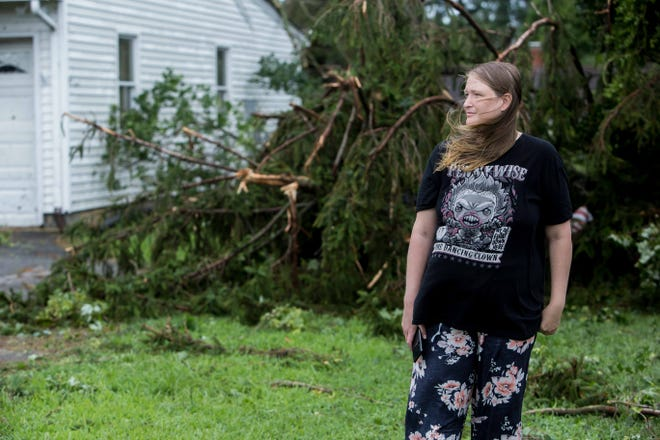 Shannon Bradford, 34, of Dover, stands in her pajamas near her neighbor's house on Lebanon Road, looking at the wreckage from her neighbor's property caused by Tropical Storm Isaias on Tuesday, Aug. 4.