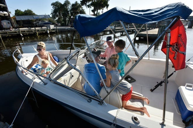 Chris Vann (background), owner of Jax Boat Rentals, goes over the operations of a rental boat with the Gilligan family Tuesday at Goodbys Creek. Vann is among the Jacksonville business owners who've noted an increase in sales during the coronavirus pandemic. [Will Dickey/Florida Times-Union]