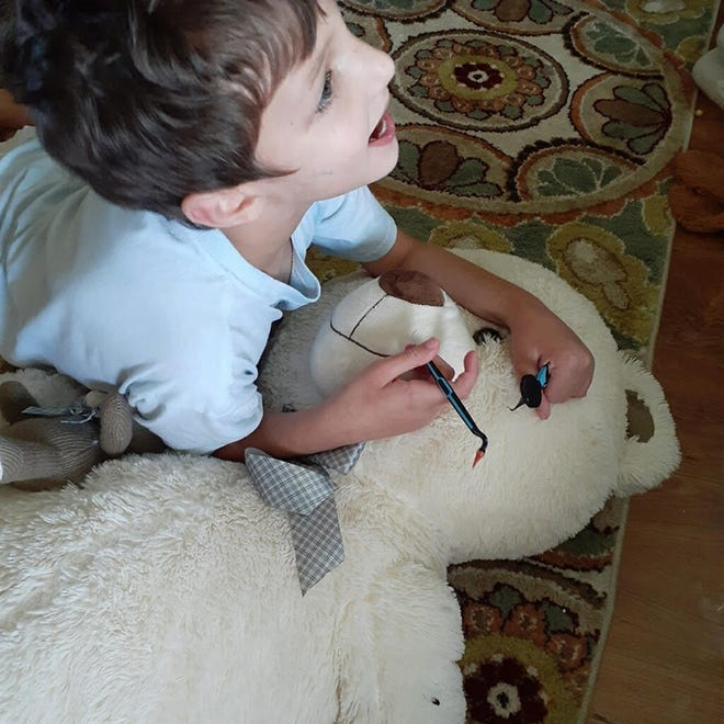 "Devyn Tate, 8, loves his ""Service Bear,"" which has a sandbag sewn inside to provide cuddles that have the weight and pressure to calm his sensory disorder. [Provided by Brittany Tate]"