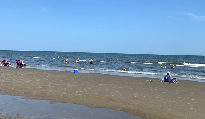 What a crowd. Friends and families enjoying the sun, sand and water at the Grand isle beach.
