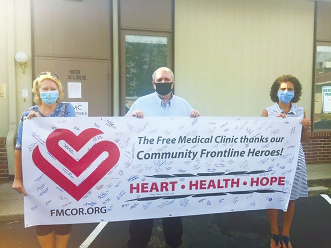 A 'Thank You' banner with many essential workers signatures is held by FMC Director Billy Edmonds, center, and 2020 FMC Bash Co-Chairs Trish Polfus, right, and Becky Dodson, left.