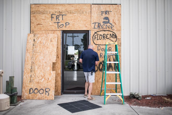 Terry Crabtree finishes boarding up the entrance to Downeast Marine in Otway, N.C., as Tropical Storm Isaias approaches Monday.