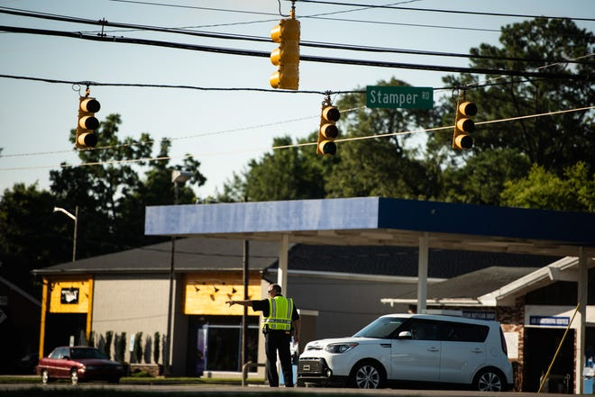 A Fayetteville police officer directs traffic at a traffic signal that is out at the intersection of Bragg Boulevard and Stamper Road on Tuesday.