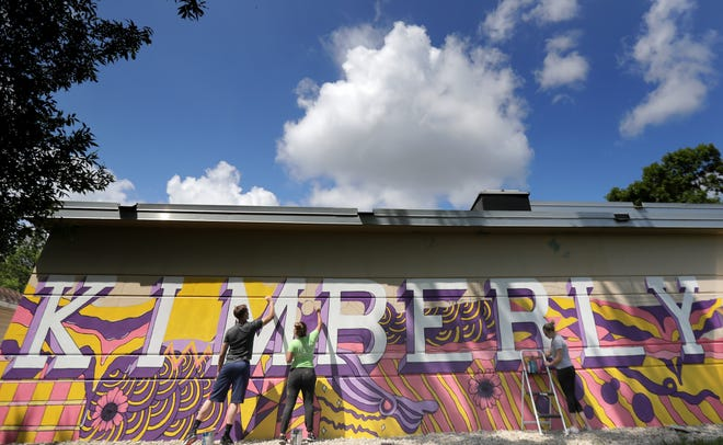 Steven Paulson, right; Hallie Dix, center; Lauren Sauter, center; and  paint a mural on the Lincoln Street pump station near Roosevelt Park on Thursday, July 30, 2020, in Kimberly, Wis.