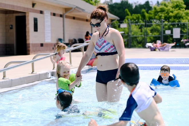County and city pools should open Memorial Day weekend and in early June, respectively. In this file photo from 2019, Lexi Williams, then 3, clings tight to her mom, Micah's, hand as she is approached by her cousin Keaton, and brother Lucas, as she walks into the shallow end of the Owen Pool.