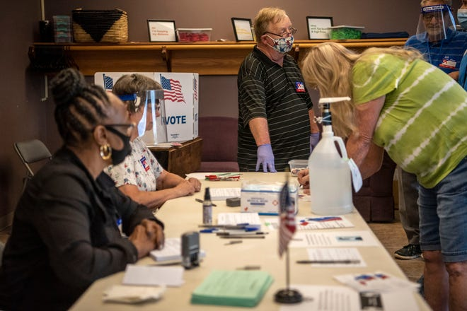 Poll workers Maxine Small, Barbara Steele and Bob Murphy assist voters for Precincts 15 & 17 at Battle Creek Community Church on Tuesday, Aug. 4, 2020 in Battle Creek, Mich.