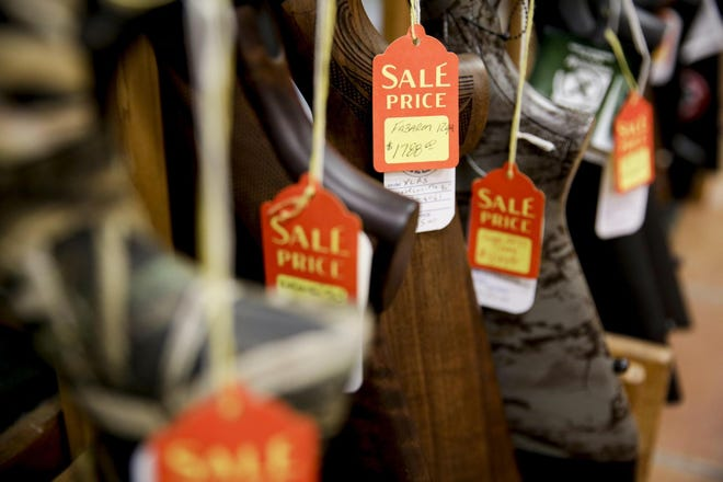 Sales tags hang from rifles at McBride's Guns and Sporting Goods in Austin on March 24.