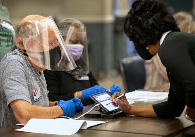 It's election day Tuesday, Aug. 4, 2020 in a few communities. Voters in St. Bernard are deciding on a 7-mill property tax renewal levy. Dave Feichdner, left and Zerita Dobbins, and all the workers are wearing masks, face shields and gloves. Everything gets wiped down after each voter signs for the ballot.