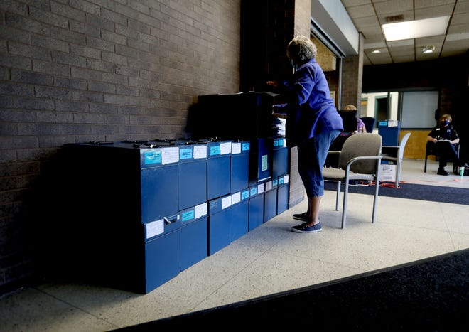 Cathy Elstone, of Livonia puts counted absentee ballots into locked blue boxes at a building at the Livonia City Hall complex in Livonia, Michigan on Tuesday, August 4, 2020 High speed scanners are used that can accurately count up to 25 ballots at a time for a quicker counting process.Over 300 volunteers are working with Livonia city clerk Susan Nash on Election Day.
