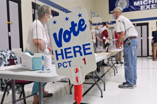 Voters and polling workers at Crissman Elementary in Shelby Township use social distancing and plexiglass barriers at the 1st Precinct on Tuesday, August 4, 2020.