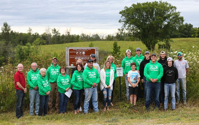 """Friends and family of Trent Schueffner gathered around an """"Adopt a State Wildlife Area"""" sign at its dedication at Mullet Creek Wildlife Area in Fond du Lac County Aug. 3. Schueffner was killed in a hunting accident on the morning of his team's level two playoff game in October 2018."""