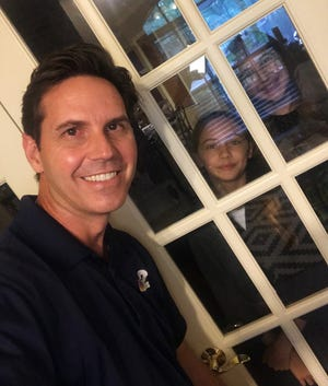 Peter Busch, weekday co-anchor for NBC-2 News, poses with his daughters Vienna and Victoria from two different sides of the glass door in the room where he is spending his time while in quarantine.