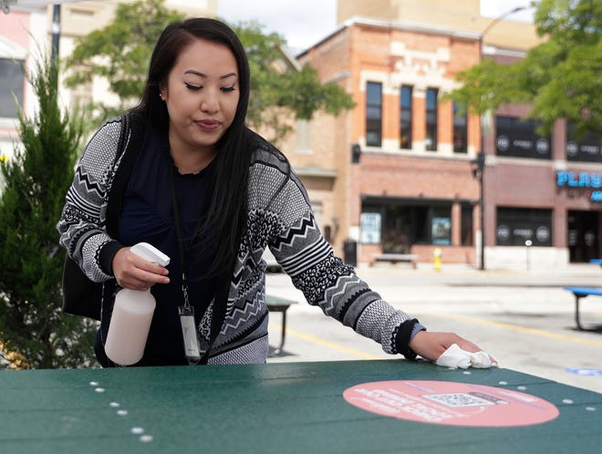 Green Bay resident Shinie Tho uses the provided sanitation supplies to clean her table at the new Downtown Dining Room, 20 parking stalls converted into an outdoor dining space on Aug. 4, 2020, in Green Bay, Wis.