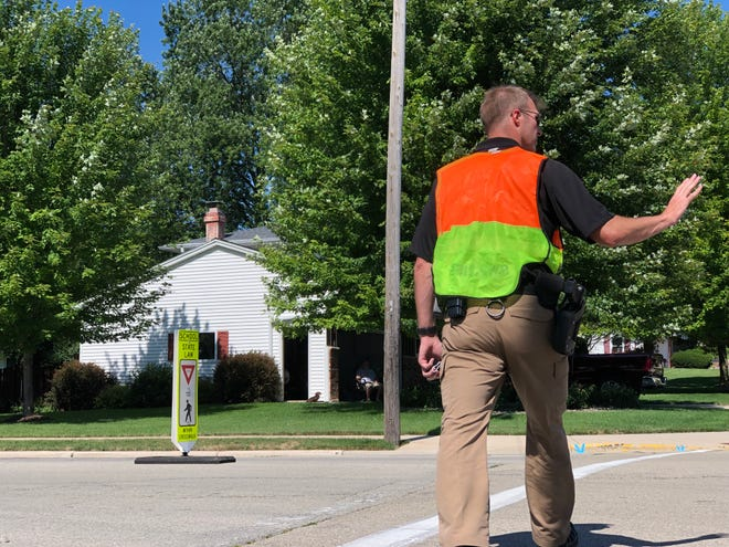 A Brown County Sheriff's officer works a Frogger safety effort July 21 at Libal Street and Greene Avenue in Allouez.