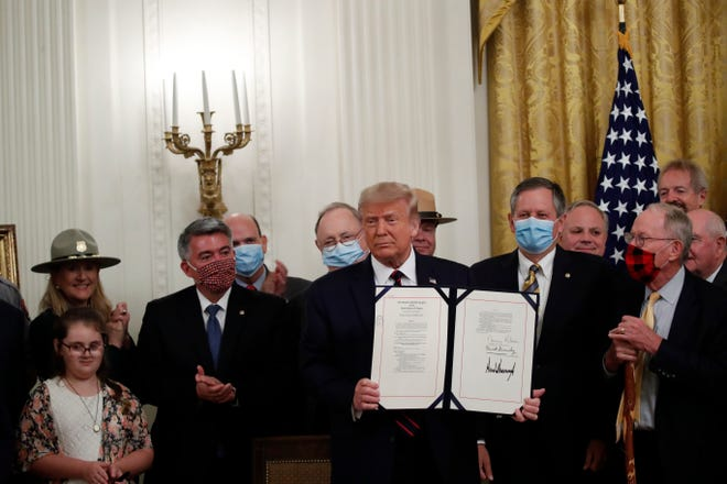 "President Donald Trump poses for a photo during a signing ceremony Tuesday for ""The Great American Outdoors Act,"" in the East Room of the White House. At right is Sen. Steve Daines, R-Mont."