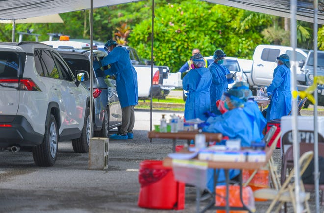 GovGuam health professionals and volunteers collect data and swab samples from residents during a drive-through extended outreach for free COVID-19 testing at the Our Lady of Peace and Safe Journey Catholic Church in Chalan Pago in this Aug. 4 file photo.