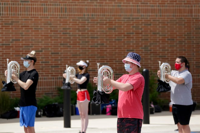 Masked brass with protective cloth over the openings of their instruments walk through visuals during a Lafayette Jefferson High School band practice, Tuesday, Aug. 4, 2020 in Lafayette.