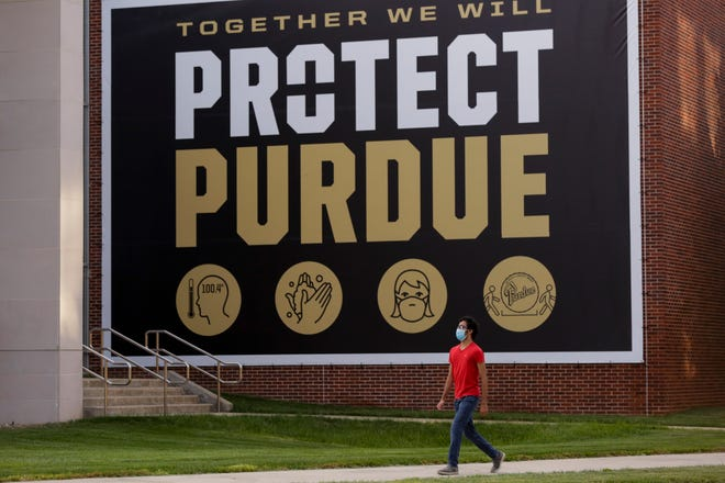 "A student walks the France A. Córdova Recreational Sports Center and a banner that reads ""together we will protect Purdue,"" Monday, Aug. 3, 2020 at Purdue University in West Lafayette."